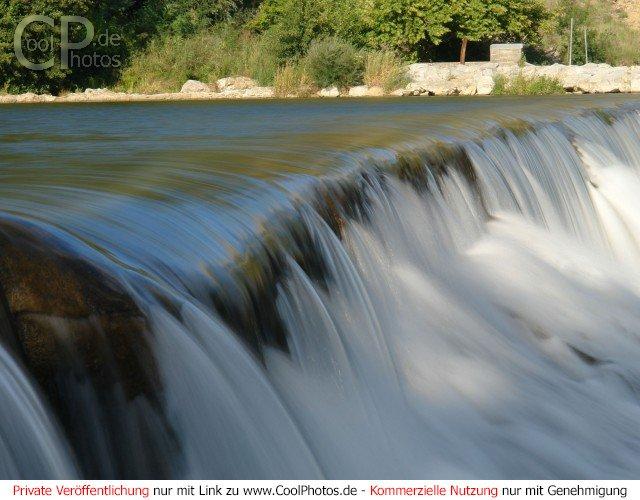 Das Wasser der Ardèche fließt einen kleinen Wasserfall hinab.