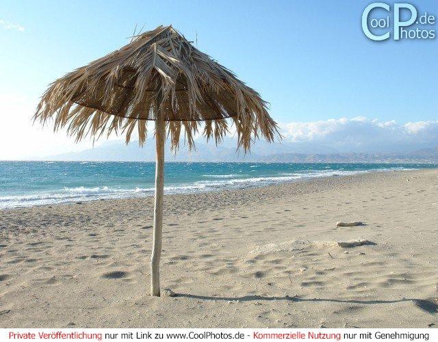Sonnenschirm am Strand mit dem Meer im Hintergrund