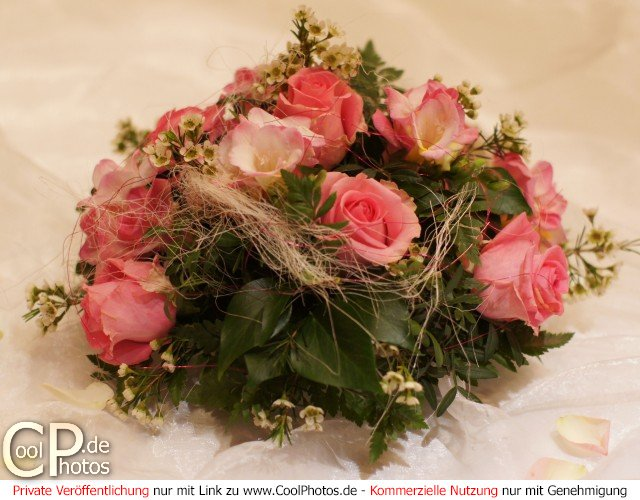 Blumenstrauß, der sich überwiegend aus rosafarbenen Rosen zusammensetzt.