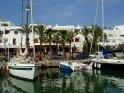 Schiffe im Hafen Cala Llonga mit Palmen im Hintergrund