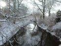 Blick über einen von verschneiten Büchen und Bäumen gesäumten Bach
