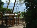Foto von einem Tisch mit vier Stühlen in einem Restaurant direkt am Meer. Im Hintergrund ist der idyllische Ausblick zu erkennen.