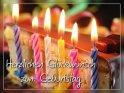 Ein Stück Geburtstagstorte mit brennenden Kerzen und dem Spruch  Herzlichen Glückwunsch zum Geburtstag