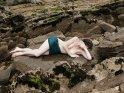Teilaktfoto einer auf Felsen liegenden Frau