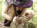 Frau im Hexenkostüm schaut in eine Glaskugel