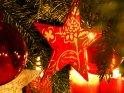 Roter Stern mit goldenen Symbolen an einem Tannenzweig. Im Hintergrund sind mehrere brennende rote Kerzen zu sehen.