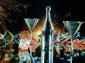 Silvesterfoto mit Glücksschwein, Sektflasche, Gläsern, Luftschlangen, Konfetti und brennenden Wunderkerzen auf einer Spiegelfläche