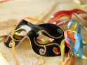 Schwarze Karnevalsmaske mit Luftschlangen