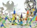 Drei lustige bunte Clownfiguren aus Glas umgeben von Luftschlangen und Konfetti. Im Hintergrund sind zwei silberne Masken zu sehen.