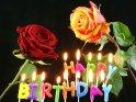Geburtstagskarte mit brennenden Geburtstagskerzen und zwei Rosen. Die Kerzen bilden den Spruch Happy Birthday.