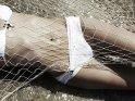 Eine Frau in einem weißen Bikini liegt, mit einem Netz bedeckt, auf einem steinigen Untergrund. Das über den Boden fließende flache Wasser glizert in der Sonne.