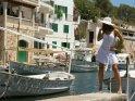 Frau im weißen Kleid steht im Hafen bei den Schiffen