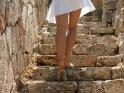 Die Beine einer Frau im weißen Kleid, die eine Natursteintreppe hinaufläuft