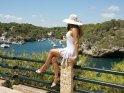 Eine Frau im weißen Kleid mit weißem Hut sitzt oberhalb der Bucht auf einem Zaunpfeiler und schaut auf die Bucht hinab.