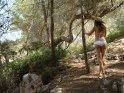 Frau im Bikini in den Bäumen hinter der Bucht