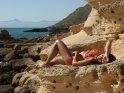 Gut gebräunte Frau im Bikini liegt an der Küste auf Sandsteinfelsen und sonnt sich.