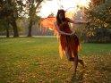 Frau im Teufelsfeenkostüm steht im Park und hält sich an einem Zweig fest, während sie verführerisch in die Kamera schaut. Die hinter ihr stehende Sonne bringt die Flügel und Teile des Kleides zum leuchten.