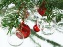 Transparente und rötlich gefärbte Glaskugeln hängen an den Zweigen eines Weihnachtsbaums.