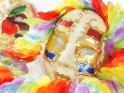 Faschingsfoto mit einer Venezianischen Maske umgeben von einer Hawaii-Kette. Im Hintergrund ist eine weitere Maske zu erkennen.