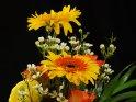 Blumenstrauß mit Gerbera und Rosen vor schwarzem Hintergrund