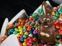 Foto von einem Schokohasen, der in einem mit zahlreichen bunten Schokoladeneiern gefüllten Riesen-Osterei steht.