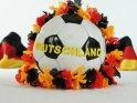 Von Deutschlandflaggen und einer Girlande in Schwarz-Rot-Gold umgebener Fußball mit dem Schriftzug ´Deutschland´.