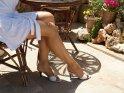 Frau im weißen Sommerkleid sitzt an einem Tisch