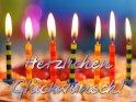 Eine Reihe von brennenden Kerzen auf einer Erdbeertorte. Die Karte ziert der Schriftzug Herzlichen Glückwunsch!