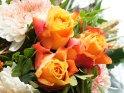 Foto von einem Blumenstrauß mit drei gelb-orange-roten Rosen