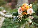 Auf einem Zaun liegender herbstlichter Blumenstrauß
