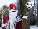 Cooler Nikolaus wirft einen Fußball durch die Luft.