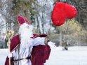 Der Nikolaus steht in einem verschneiten Park und wirft ein großes rotes Stoffherz durch die Luft. Dabei fliegen Schneeflocken vom Herz weg.