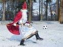 Mit einem Fußball im Schnee spielender Nikolaus