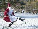 Der Nikolaus geht mit der Zeit und spielt auf einer verschneiten Wiese Fußball.