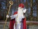 Nikolaus steht winkend vor einigen Bäumen.