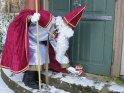 Der Nikolaus stellt einen gefüllten Stiefel vor eine historisch anmutende Tür. Am boden ist passend zur Jahreszeit eine dünne Schneedecke zu erkennen.