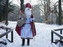 Der Weihnachtsmann läuft, mit Geschenken bepackt, durch den Schnee.