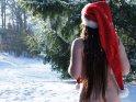 Aktfoto einer Frau, die nur mit Weihnachtsmütze und Schal bekleidet im Schnee steht.