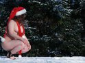 Aktfoto von einer im Schnee hockenden Frau mit Weihnachtsmütze und Schal.