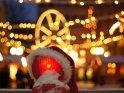Weihnachtsmütze sitzt auf einem teilweise mit Schnee bedeckten roten Straßenlicht. Im Hintergrund sind unscharf die Lichter eines Weihnachtsmarktes zu erkennen.