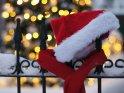 Weihnachtsmütze und Schal liegen auf einem eingeschneiten Gitterzaun. Im Hintergrund sind die strahlenden Lichter eines Weihnachtsbaums zu sehen.    Dieses Motiv findet sich seit dem 23. Dezember 2010 in der Kategorie Weihnachtsbilder.