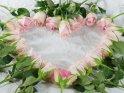 Zu einem Herz gelegte weißrosa Rosen