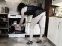 Foto einer Frau in Dessous und Highheels, die eine Pizza aus dem Backofen holt