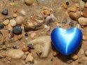 Blaues Herz liegt zwischen kleinen Steinen am Strand