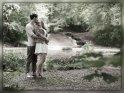 Küssendes Paar an einem von Bäumen umgebenen See