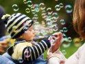 Baby wird von der Mutter gefüttert, während es von Seifenblasen umgeben ist.