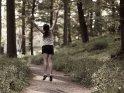 Eine junge Frau springt auf einem Waldweg vor Freude in die Luft.    Aus der Kategorie Sonstige Personenfotos