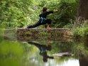 Eine Kung Fu Kämpferin posiert auf einer niedrigen Mauer und spielt sich im davor befindlichen Wasser.