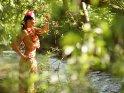 Eine Frau steht, bekleidet mit einem Bastrock und einer Hawaiikette, in einem kleinen Fluß.