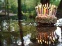 Geburtstagskuchen mit brennenden Kerzen spiegelt sich im Wasser